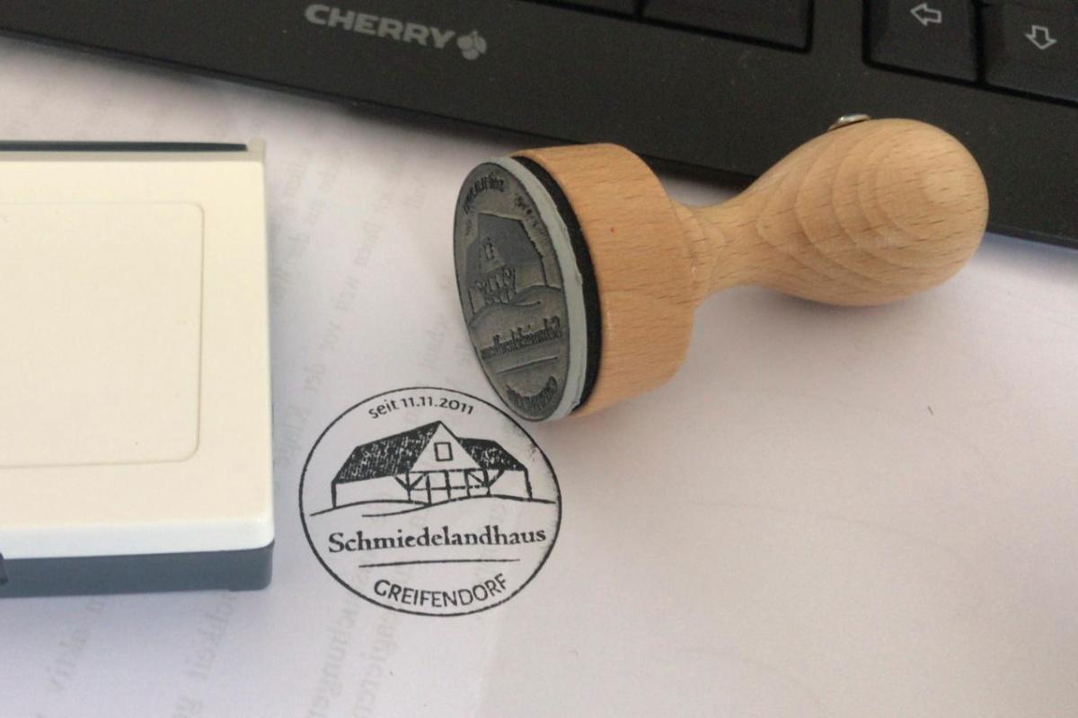 runder Holzstempel mit Logo für Schmiedelandhaus Greifendorf